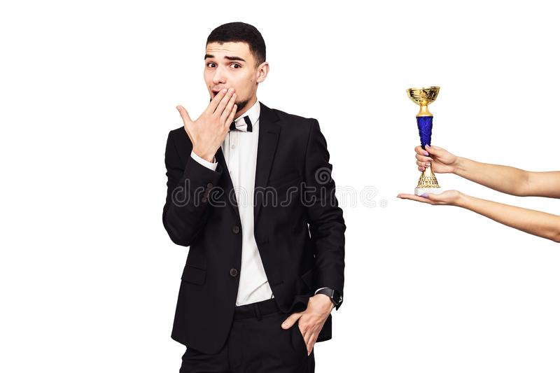 Handsome bearded man in a black suit is handed the champion cup. The guy is very sincerely happy about winning. Isolated on white royalty free stock photos
