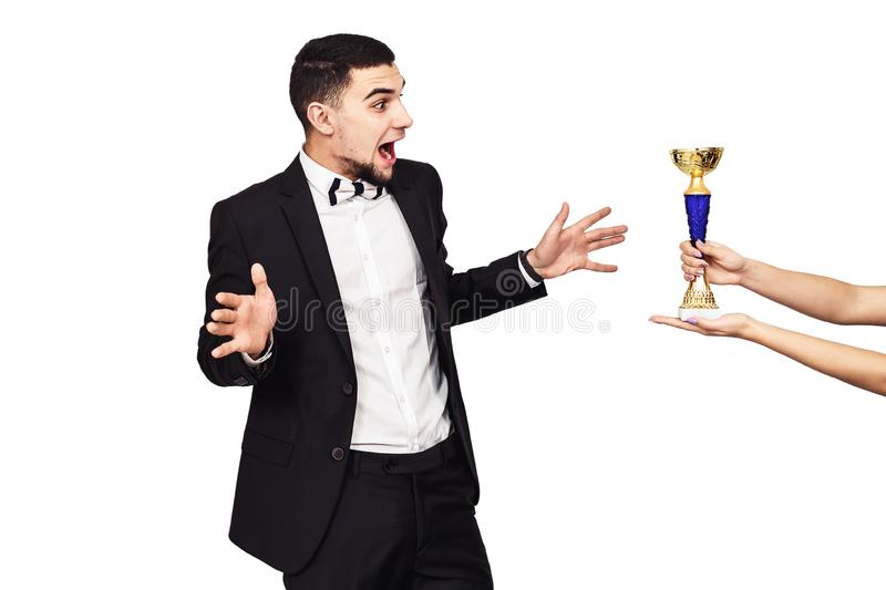 Handsome bearded man in a black suit is handed the champion cup. The guy is very sincerely happy about winning. Isolated on white stock photo