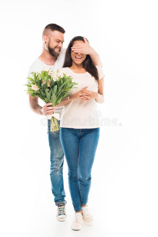 Handsome bearded man with bouquet of flowers covering his girlfriends eyes,. Handsome bearded men with bouquet of flowers covering his girlfriends eyes, isolated stock photo