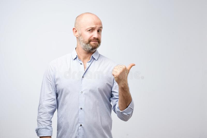 Handsome bearded man in casual clothes is pointing awaywith thumb looking at camera on gray background. Like saying Do not miss this offer stock photography