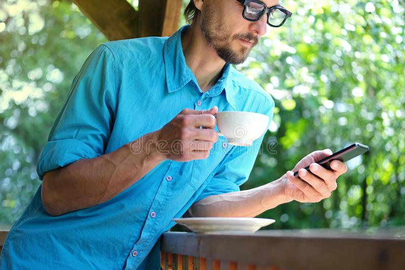 Handsome bearded man in casual wear with glasses drinking coffee and uses smartphone in summer open terrace cafe stock images
