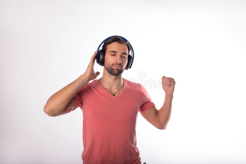 Handsome bearded man dancing and enjoying cool music via wireless headphones while standing isolated in studio stock images