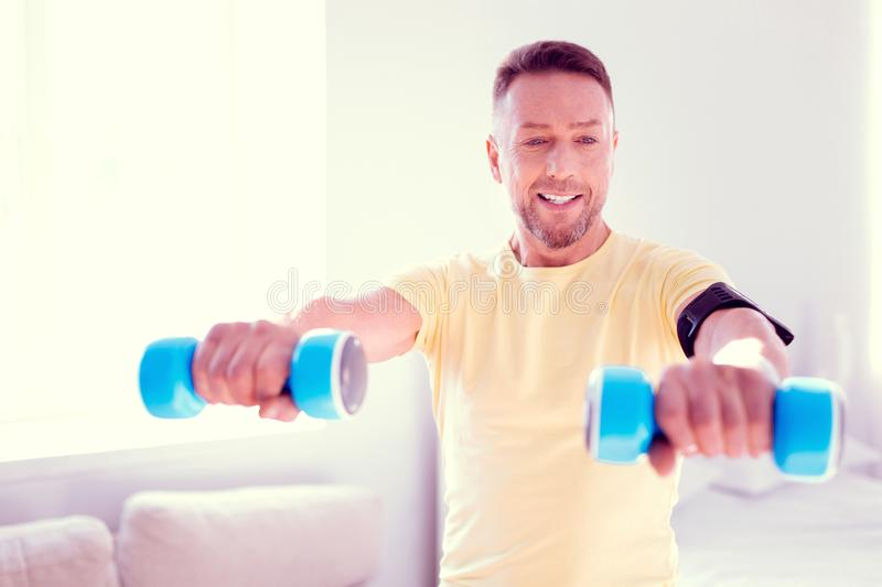 Handsome bearded man doing morning exercises at home before going to work stock images