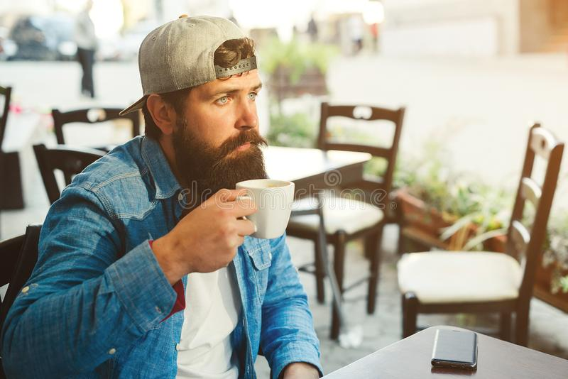Handsome bearded man drinking coffee outdoor cafe. Hipster man wears denim jacket and cap. Urban street style. Coffee break time stock photo