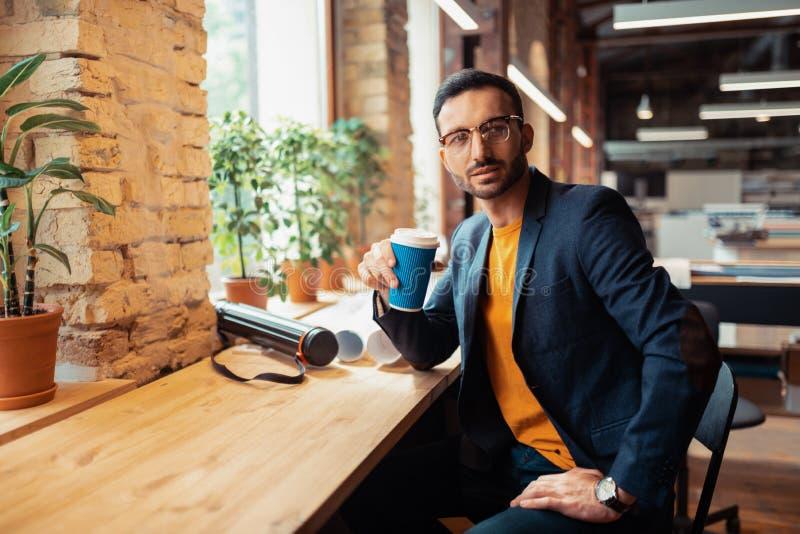 Handsome bearded man drinking coffee sitting near window royalty free stock photo