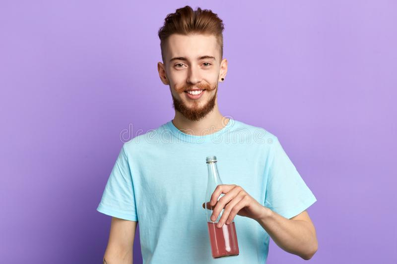 Handsome bearded man enjoying drinking juice royalty free stock images