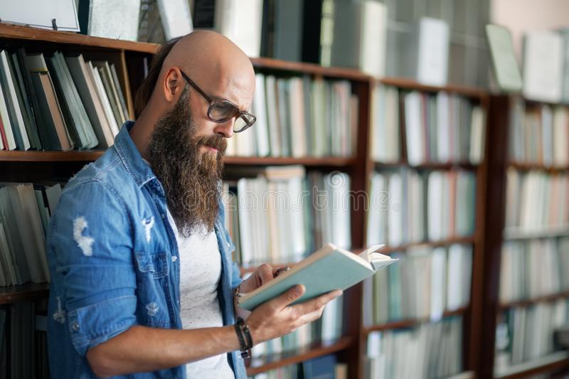 Handsome bearded man in glasses reading book in library royalty free stock photo