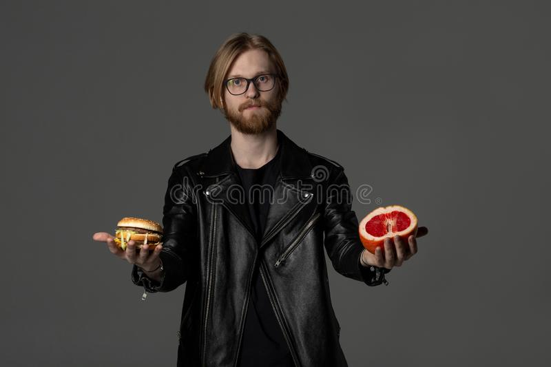 Handsome bearded man in glasses, wearing black leather jacket stock image