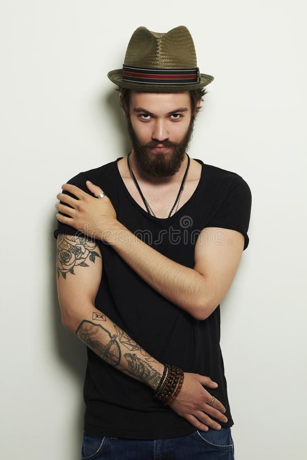 Handsome bearded man in hat.Brutal boy with tattoo stock photography