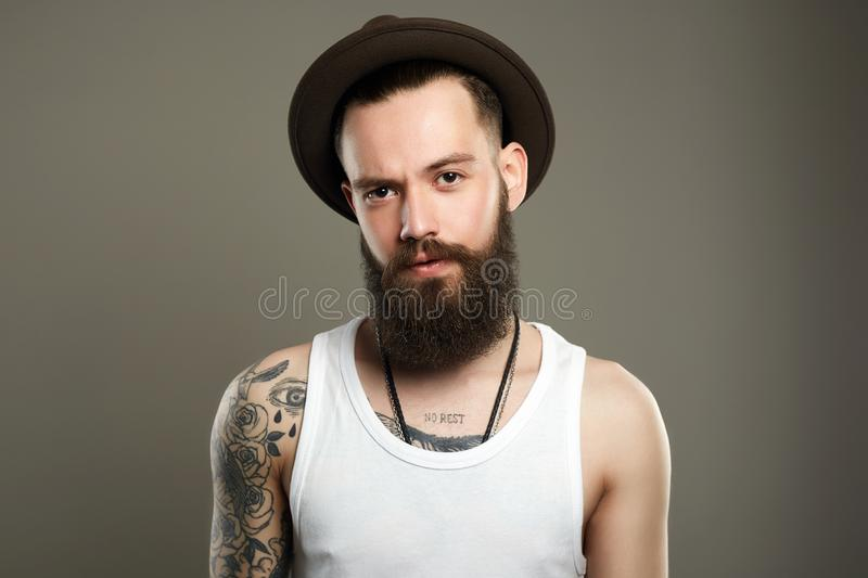 Handsome Bearded Man in Hat. Fashion boy with tattoo royalty free stock photos