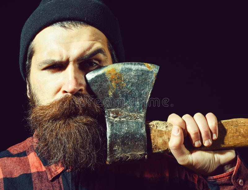 Handsome bearded man in hat holds axe on black background royalty free stock photos