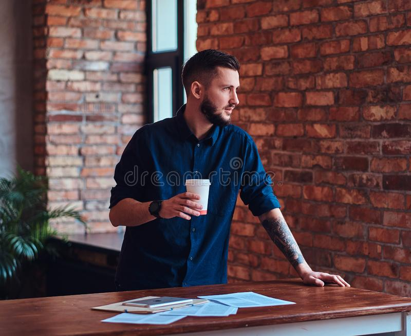 Handsome bearded man holds takeaway coffee and working with paper documents in the office with loft interior. stock photography