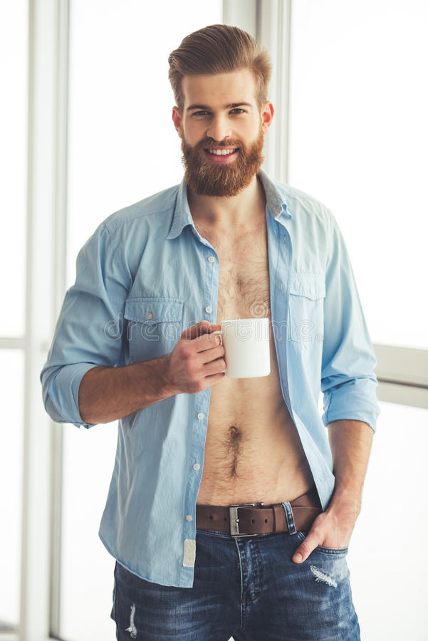 Handsome bearded man at home stock image