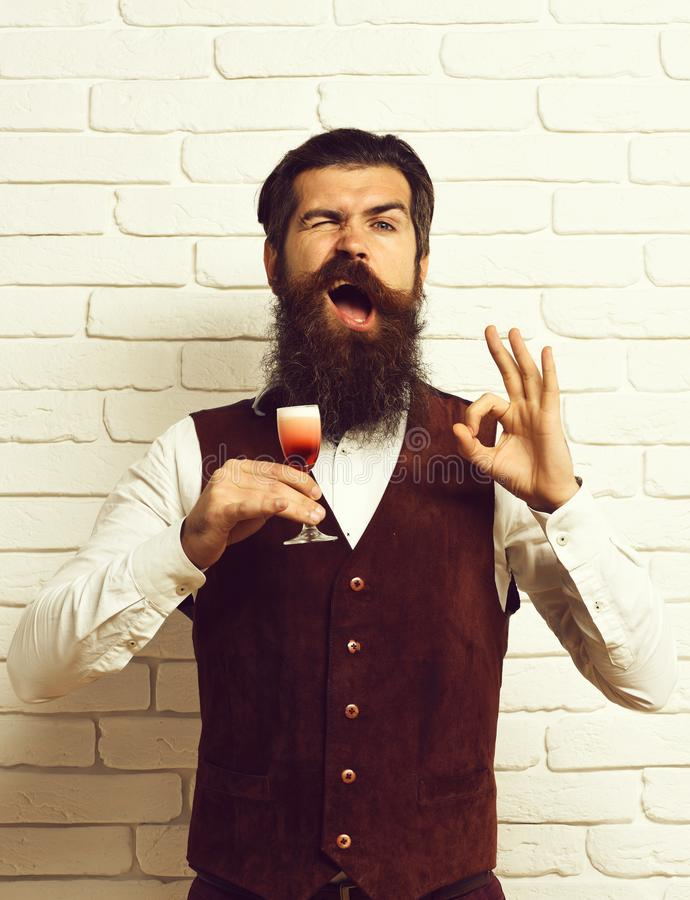 Handsome bearded man with long beard and mustache has stylish hair on funny face holding glass . royalty free stock image
