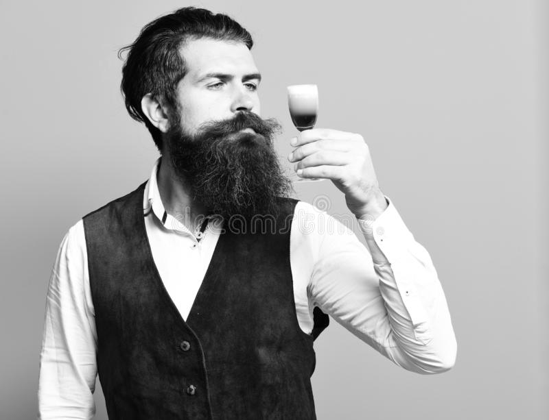 Handsome bearded man with long beard and mustache on serious face tasting glass of alcoholic shot in vintage suede stock image