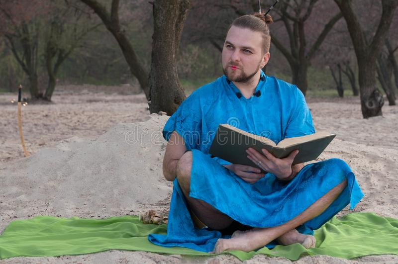 Handsome bearded man with make up, bun on head in blue kimono sitting, holding opened large book stock image