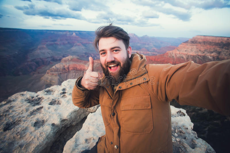 Handsome bearded man makes selfie photo on travel hiking at Grand Canyon in Arizona stock image