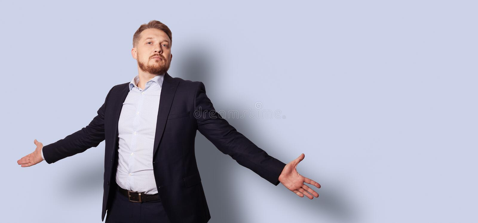 Handsome bearded man with open arms in a suit without a tie. Studio portrait over gray blue background stock photos