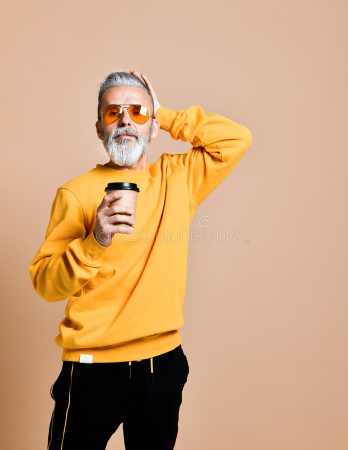 Handsome bearded man with paper cup of morning coffee royalty free stock images