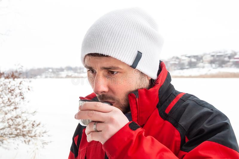 Handsome bearded man in a red and black jacket and white cap drinking hot tea from a metal cup against a frozen river stock image