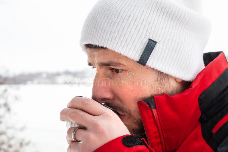 Handsome bearded man in a red and black jacket and white cap drinking hot tea from a metal cup against a frozen river stock images