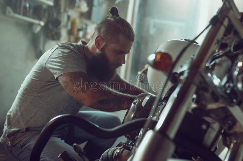 Handsome bearded man repairing his motorcycle in the garage. A man wearing jeans and a t-shirt royalty free stock image