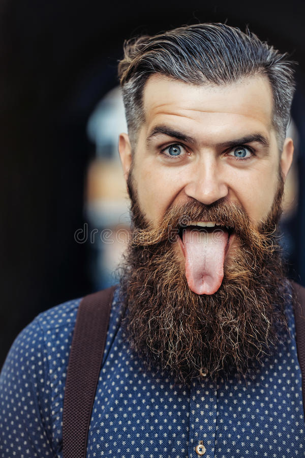 Handsome bearded man showing tongue. Young handsome bearded man portrait with long beard and moustache has stylish hairdo in shirt outdoor showing tongue on stock photos