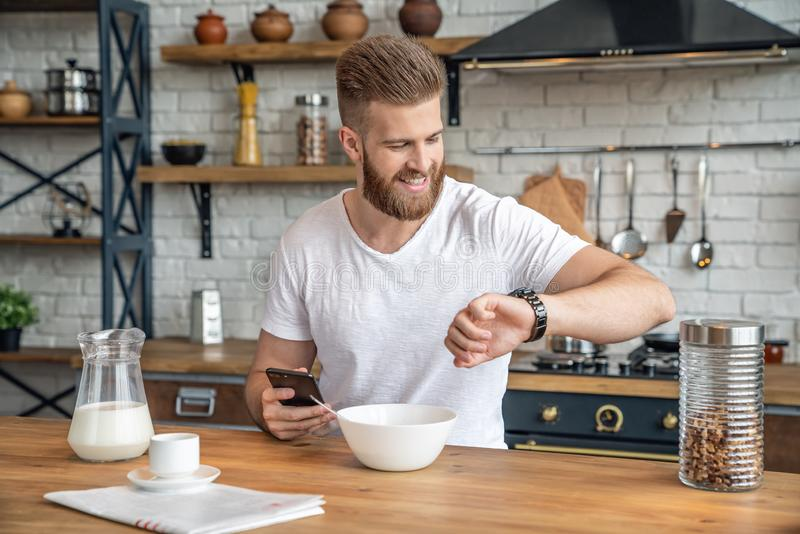Handsome bearded man is sitting in the kitchen having breakfast cereals and milk, coffee and bananas. checking his mail on the royalty free stock photo