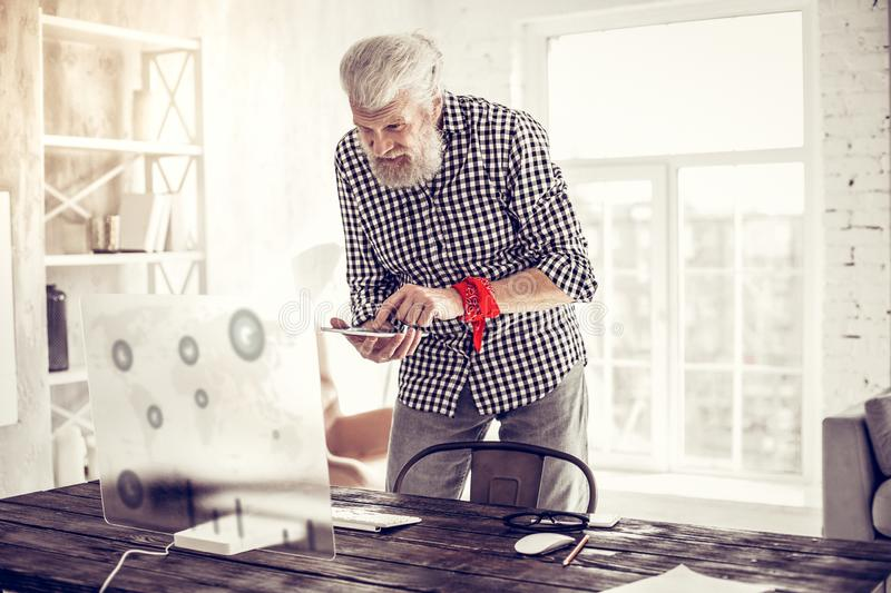 Handsome bearded man standing near his workplace. Let me check. Delighted gray-haired male person expressing positivity while looking at his device stock photography