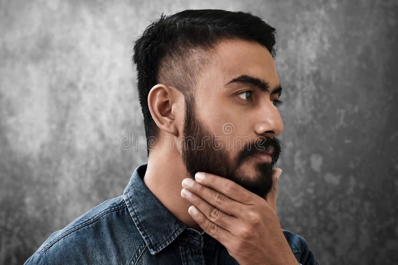 Handsome bearded man touching his beard stock image