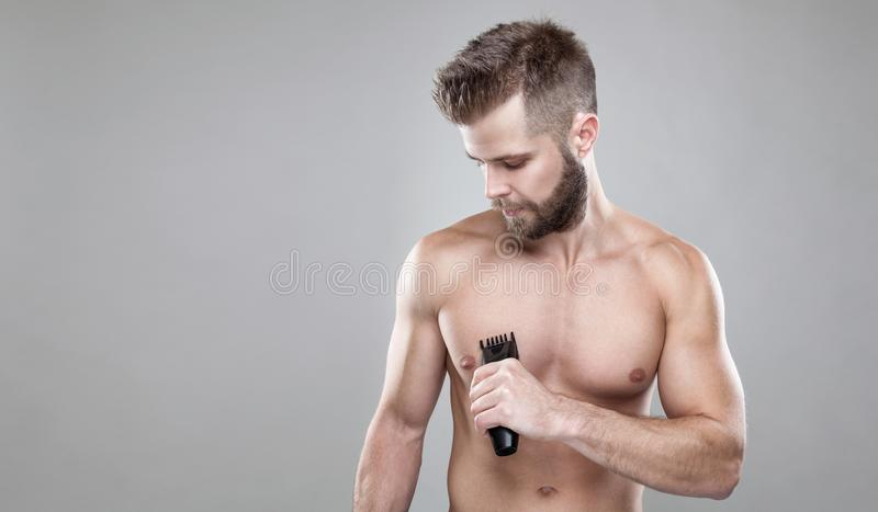 Handsome bearded man with a trimmer shaving off body hair stock photo