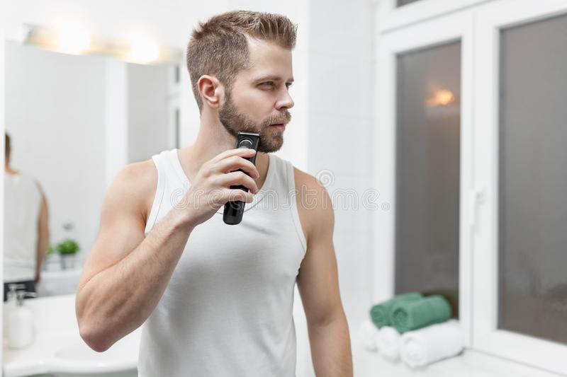 Handsome bearded man trimming his beard with a trimmer royalty free stock images