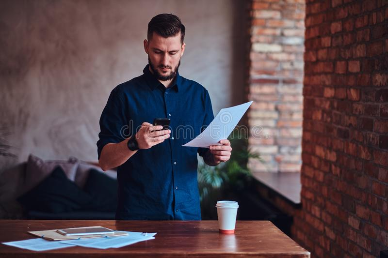 Handsome bearded man using a smartphone and working with paper documents in office with loft interior. royalty free stock image