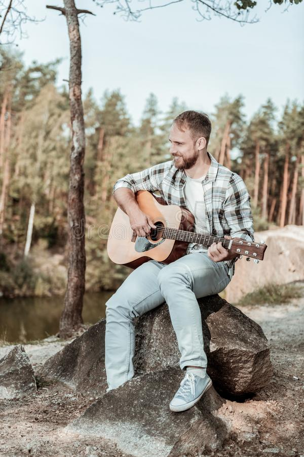 Handsome bearded man wearing jeans and squared shirt playing the guitar near lake royalty free stock photography