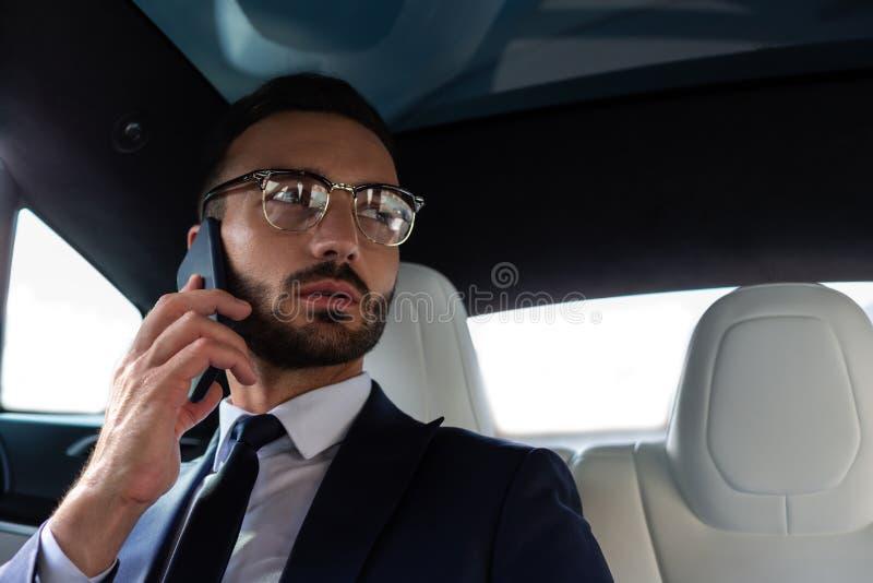 Handsome bearded man wearing suit calling secretary stock image