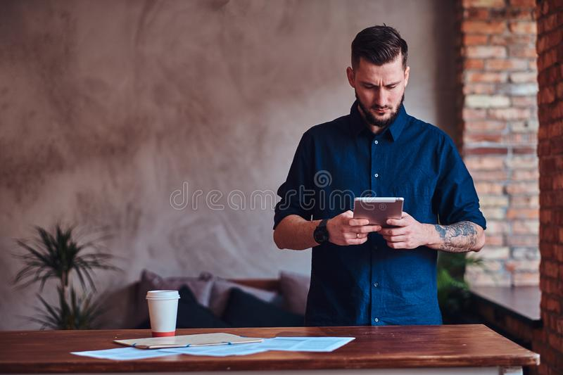 Handsome bearded man working with tablet in office with loft interior. stock image