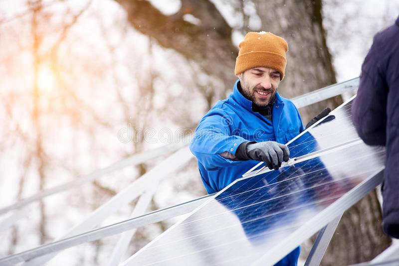 Professional electrician worker installing solar panels. Handsome bearded mature male electrician worker smiling while installing solar pannels on power plant royalty free stock photography