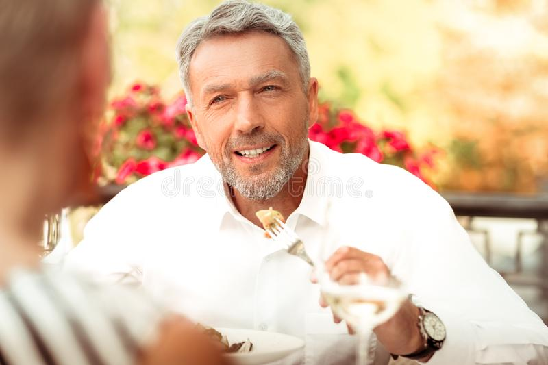 Handsome bearded mature man eating and talking to his wife royalty free stock image