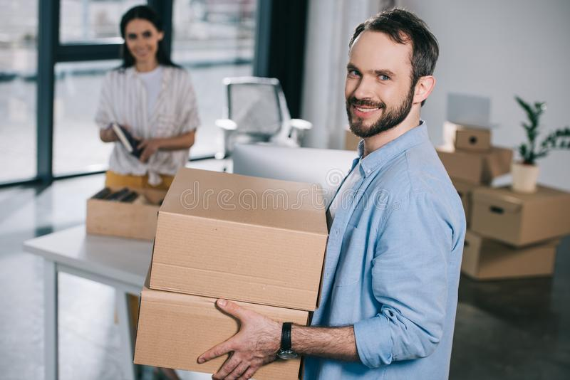 handsome bearded man holding cardboard boxes and smiling at camera while relocating with female colleague stock photos