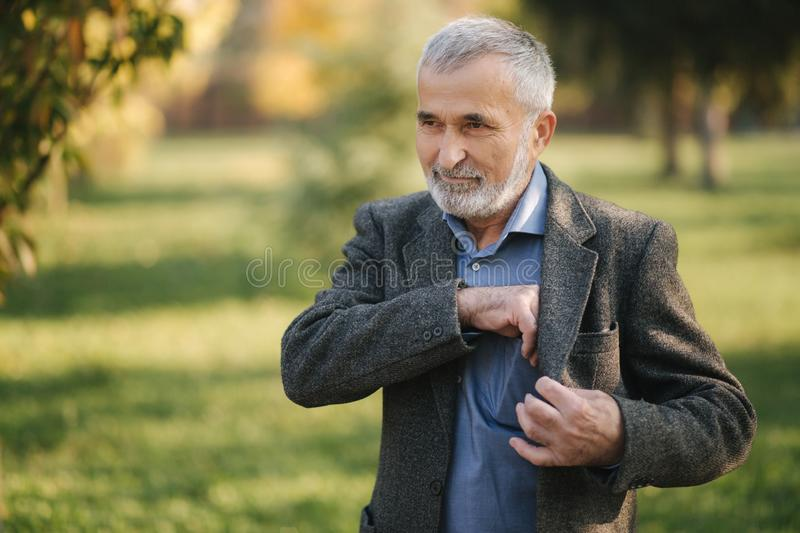 Handsome bearded old man take a smartphone from the jacket.  stock images