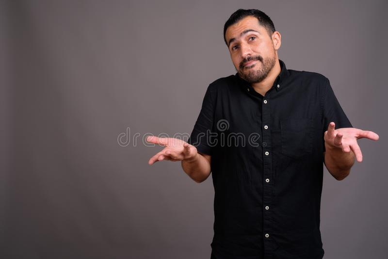 Handsome bearded Persian man against gray background. Studio shot of handsome bearded Persian man wearing black shirt against gray background royalty free stock photo