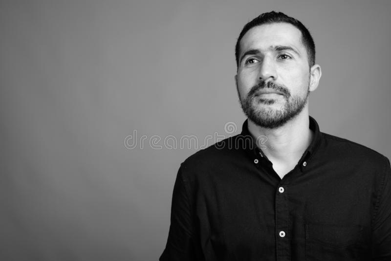 Handsome bearded Persian man against gray background stock images