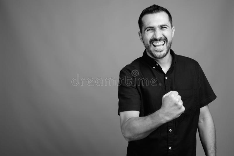 Handsome bearded Persian man against gray background royalty free stock images