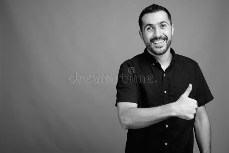 Handsome bearded Persian man against gray background stock photos