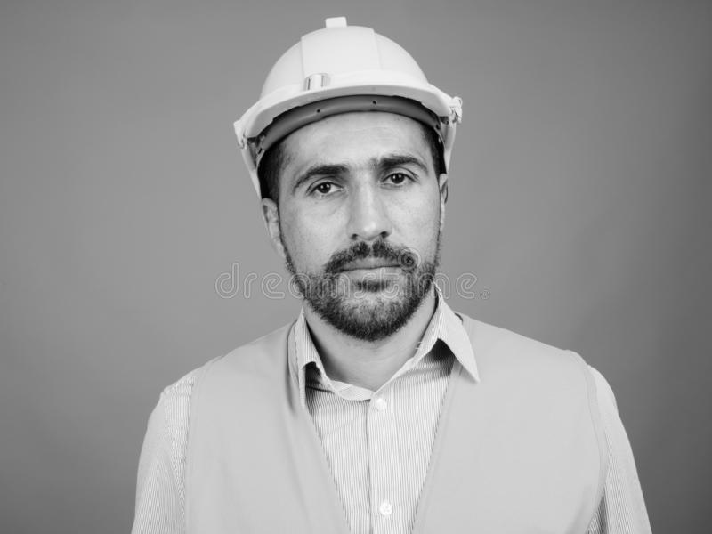 Handsome bearded Persian man construction worker against gray background stock image