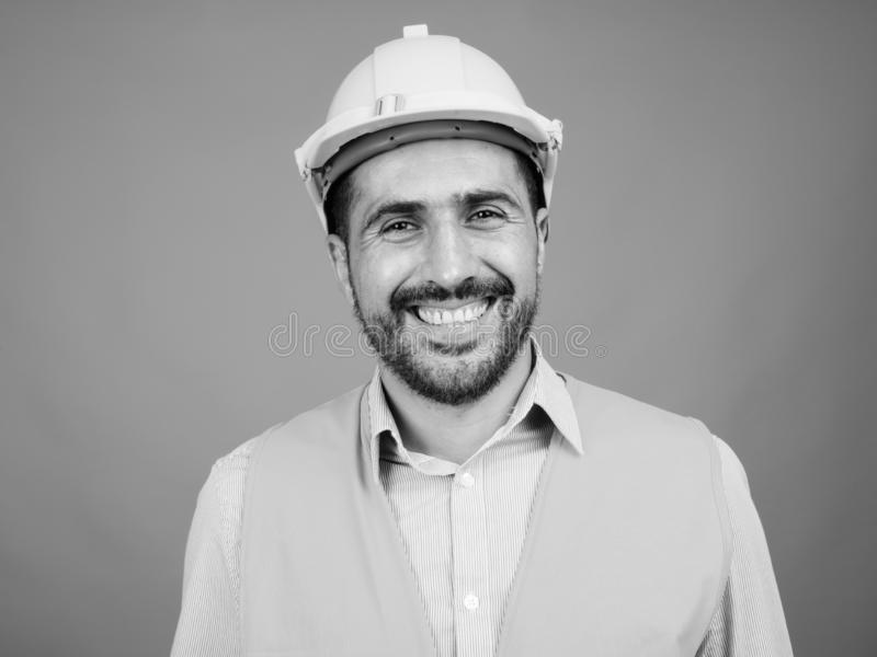 Handsome bearded Persian man construction worker against gray background royalty free stock photography