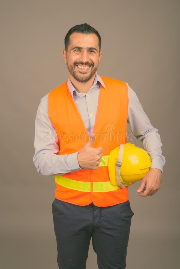 Handsome bearded Persian man construction worker against gray background royalty free stock photos