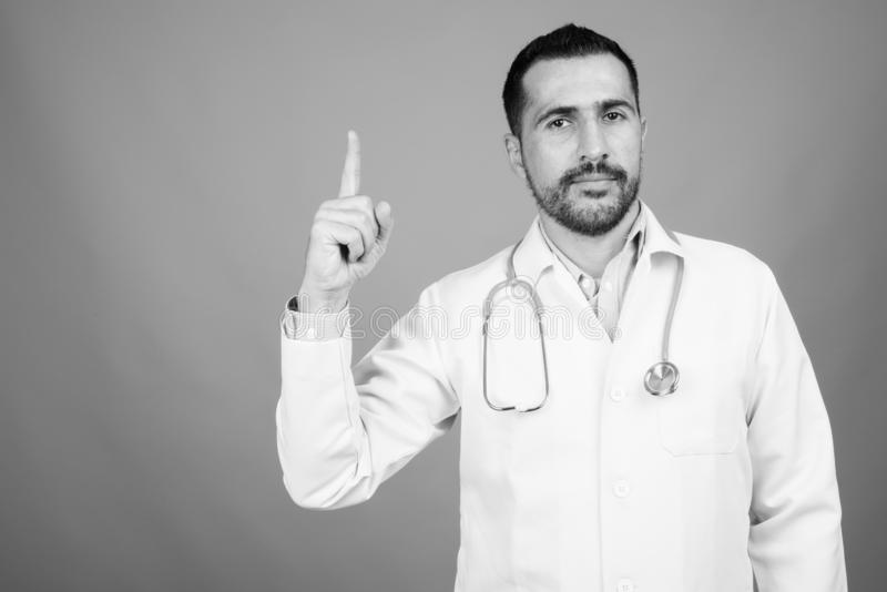 Handsome bearded Persian man doctor against gray background royalty free stock photos
