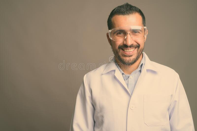 Handsome bearded Persian man doctor wearing protective glasses against gray background. Studio shot of handsome bearded Persian man doctor wearing protective royalty free stock photography