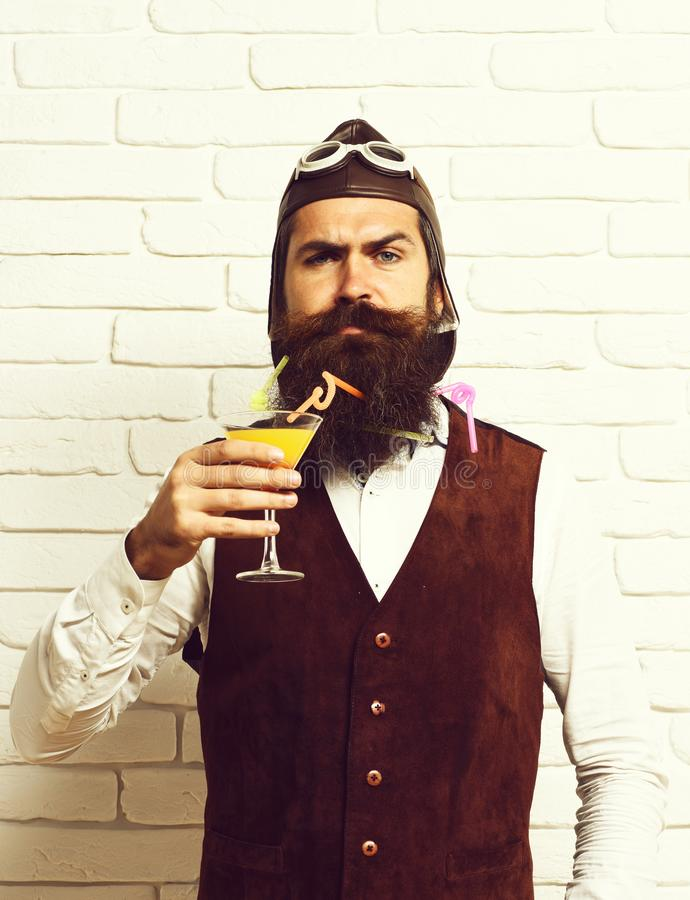 Handsome bearded pilot man with long beard and mustache on serious face holding glass of alcoholic cocktail in vintage. Suede leather waistcoat with hat and royalty free stock photo